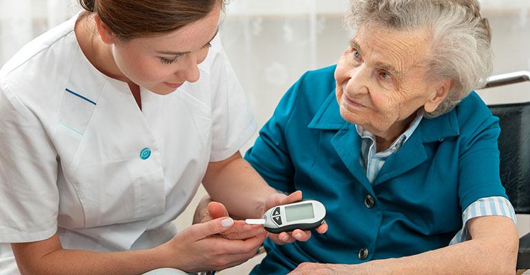 Una enfermera hace una prueba de azúcar en sangre a una persona mayor.